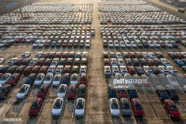 aerial view new cars lined up in the port for import and export - parkfläche stock-fotos und bilder