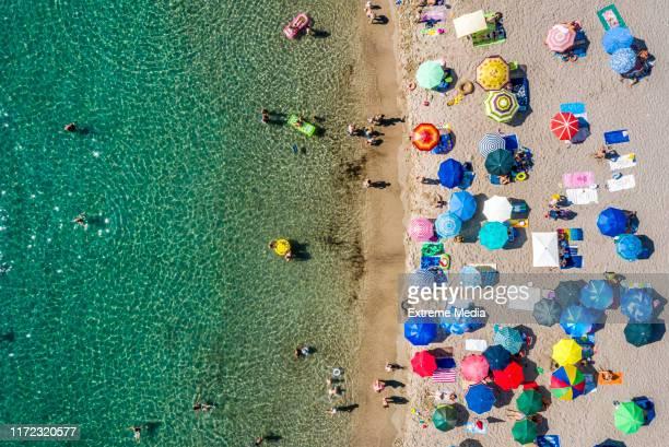 vue aérienne d'un rivage de plage d'une mer émeraude-couleur polluée - parasol photos et images de collection