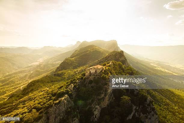Aerial view of a beautiful church on top of mountain with stunning summits on sunset light in the Catalan Pyrenees.