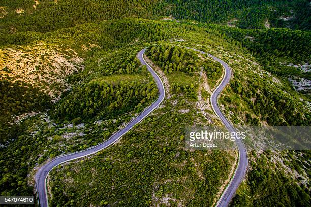 Aerial view of a beautiful curvy mountain road with nice shape between the woods in the Catalan Pyrenees during a road trip on summertime.