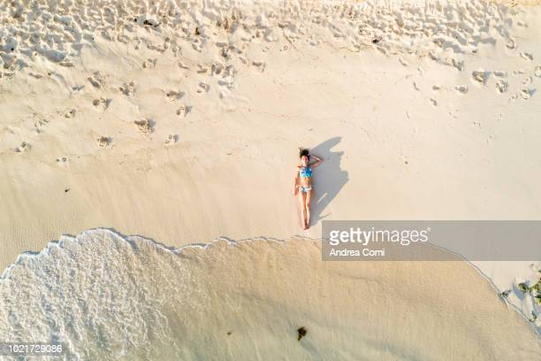 aerial view of a beautiful woman sunbathing - women sunbathing stock photos and pictures