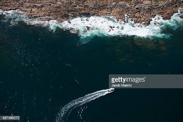 aerial view of a boat passing near rocky coastline - western australia stock pictures, royalty-free photos & images