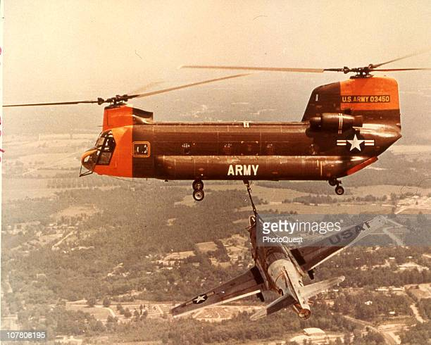 Aerial view of a Boeing CH47 Chinook helicopter as it carries an unidentified fighter plane from a tether Vietnam 1965