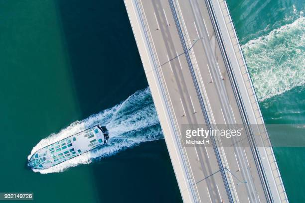 Aerial view of a bridge and a ship at sea.