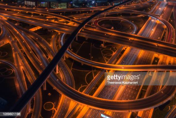 aerial view of a busy road intersection in dubai at night - railroad stock pictures, royalty-free photos & images