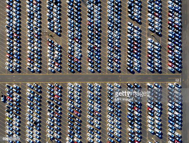 Aerial view of a car distribution centre, new cars parked in rows on a lot ready for sale.