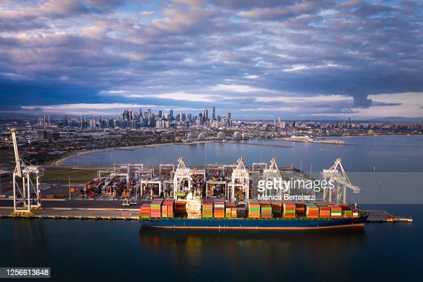 aerial view of a cargo boat and the melbourne skyline - melbourne australia stock pictures, royalty-free photos & images