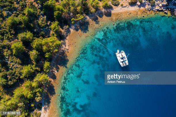 aerial view of a catamaran yacht in the blue sea. yachting, luxury vacation at sea. yachting in the caribbean - french overseas territory stock pictures, royalty-free photos & images