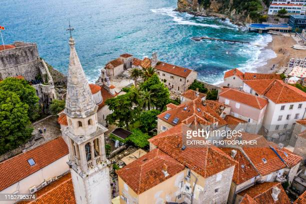 aerial view of a church bell tower rising from the rooftops of old town of budva, situated on the fortress mogren - montenegro stock pictures, royalty-free photos & images
