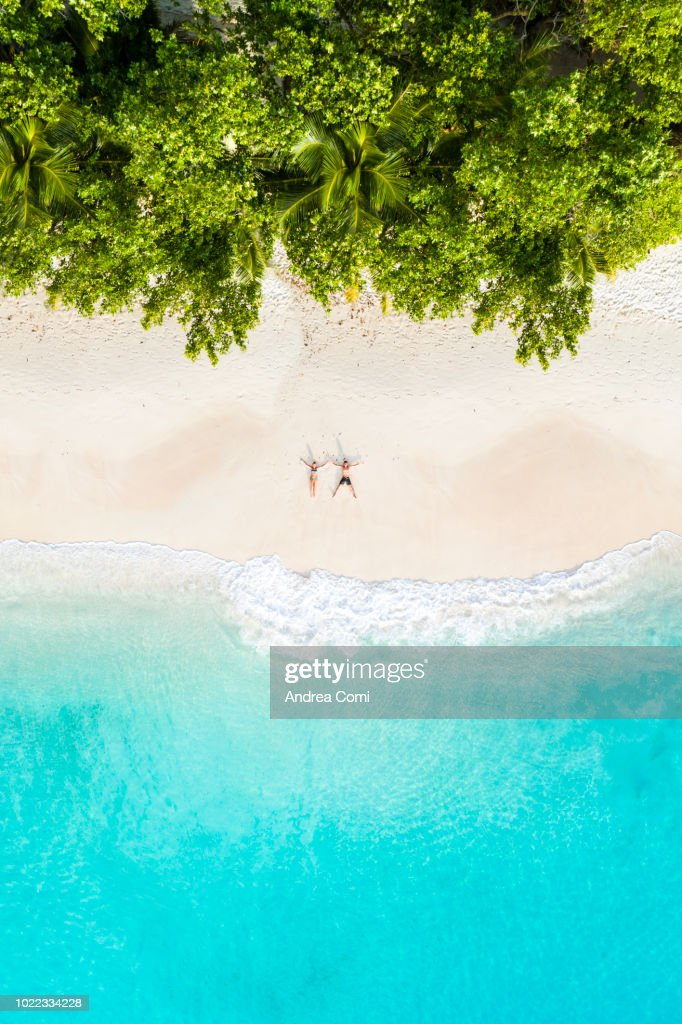 Aerial view of a couple lying down on a tropical beach : Photo