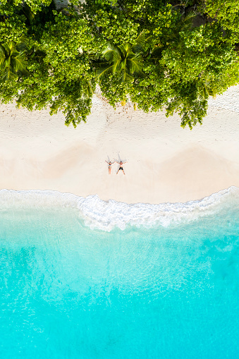 Aerial view of a couple lying down on a tropical beach - gettyimageskorea