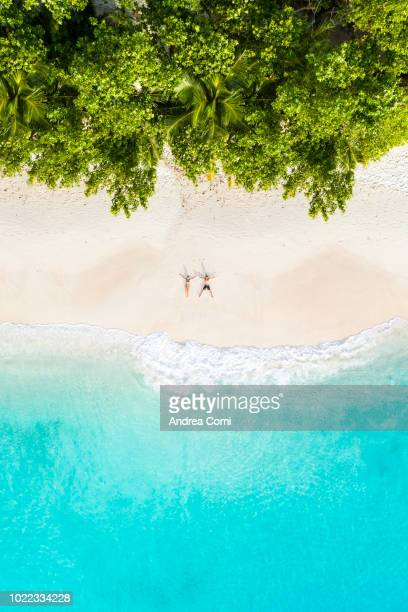 aerial view of a couple lying down on a tropical beach - escapism stock pictures, royalty-free photos & images