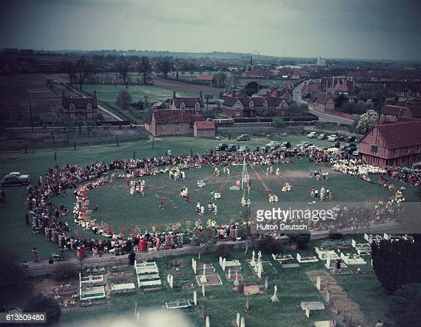 Aerial view of a crowd of people watching people dance around the Maypole in Elstow Bedfordshire