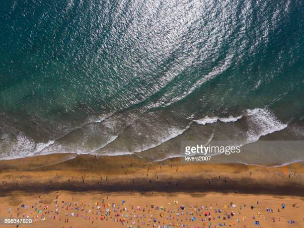 Aerial view of a crowded beach on a sunny day
