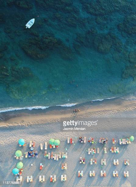 aerial view of a crowded beach, umbrellas and people on the sand - crowded beach stock pictures, royalty-free photos & images