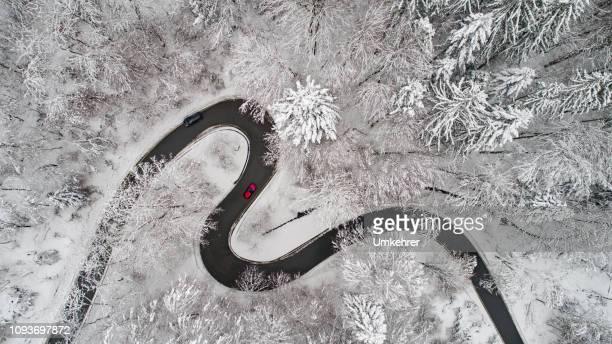 luchtfoto van een bochtige weg in de winter - drone stockfoto's en -beelden