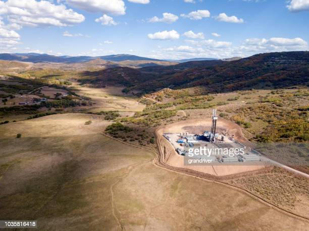 aerial view of a fracking drilling rig in the autumn mountains of colorado - drill stock pictures, royalty-free photos & images