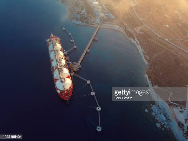 aerial view of a gas tanker moored to the jetty close to a power station during a foggy sunny day. - 液化天然ガス ストックフォトと画像