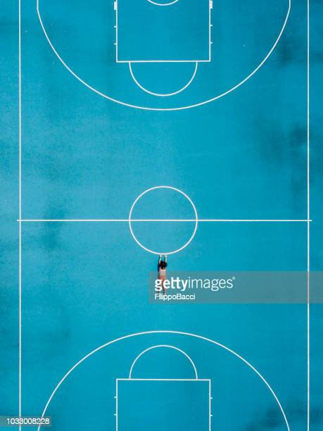 aerial view of a girl hanging in a basketball court - basketball court stock pictures, royalty-free photos & images