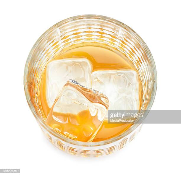 Aerial view of a glass with whiskey and ice cubes