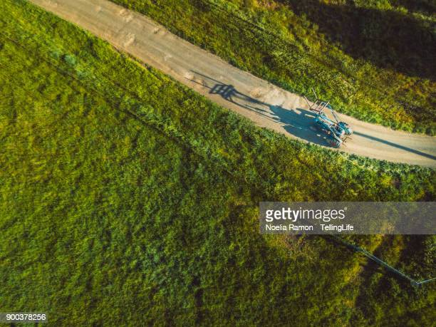 Aerial view of a grandmother driving a tractor at her family farm