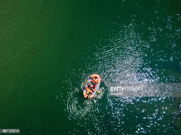 Aerial view of a group men and women rafting in a calm river