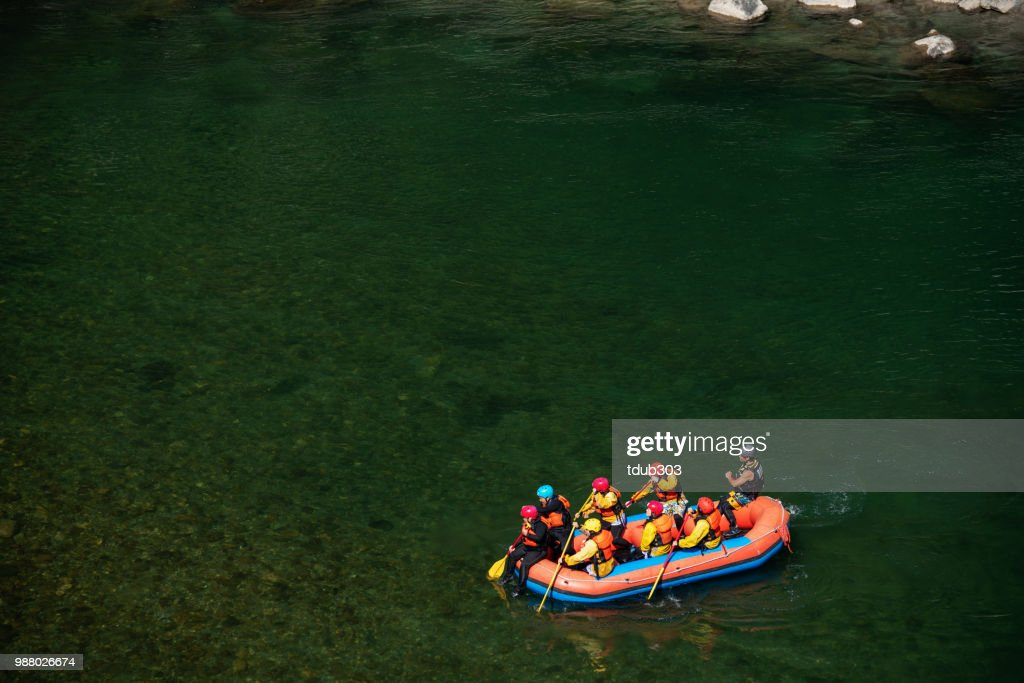 Aerial view of a group men and women rafting in a calm river : Stock Photo