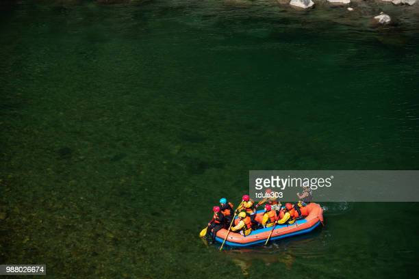 Luftaufnahme von einer Gruppe Männer und Frauen, die in einem ruhigen Fluss rafting