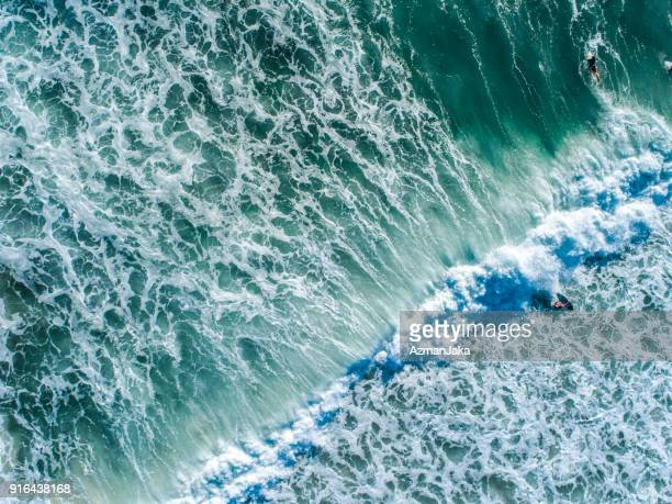 Aerial view of a group of friends in the water surfing