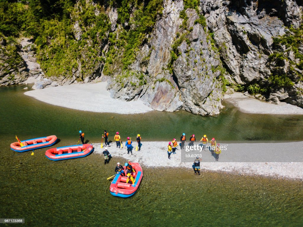 Aerial view of a group of men and women exploring an island in a river raft : Stock Photo