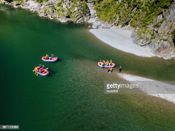 Aerial view of a group of men and women exploring an island in a river raft