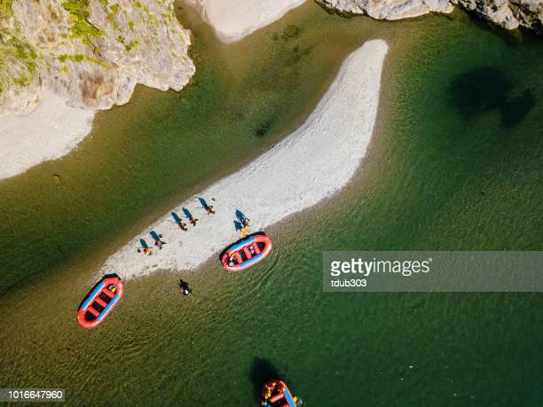 Aerial view of a group of men and women exploring an island in river rafts