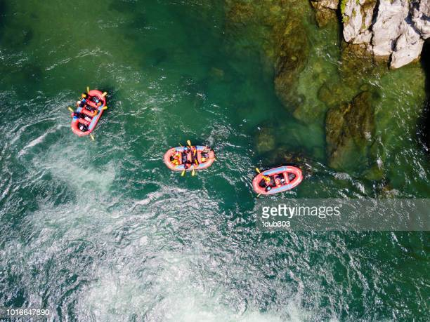 aerial view of a group of men and women in multiple boats white water river rafting - whitewater rafting stock pictures, royalty-free photos & images