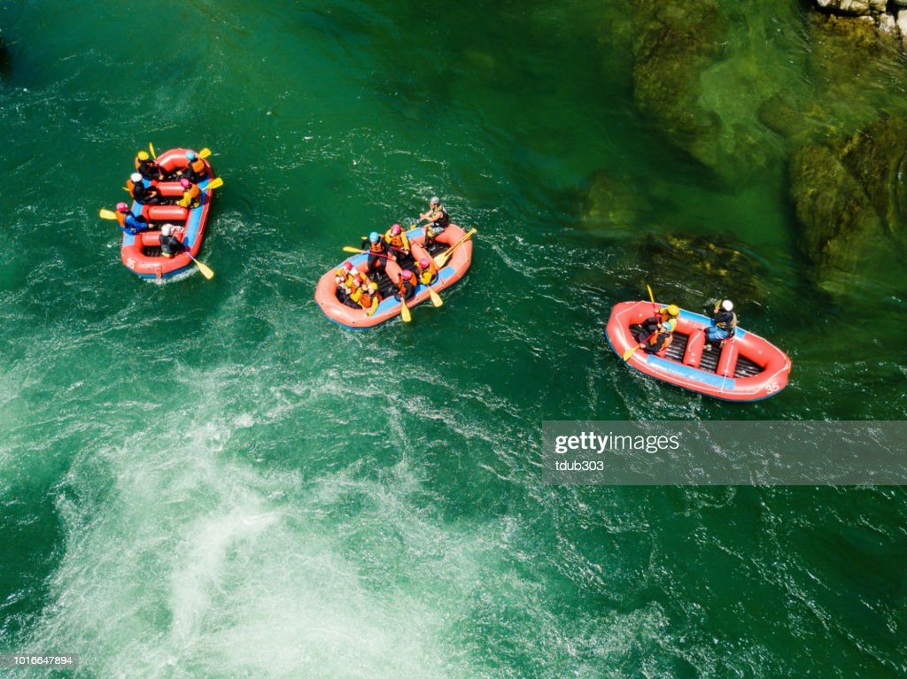 Aerial view of a group of men and women in multiple boats white water river rafting : Stock Photo