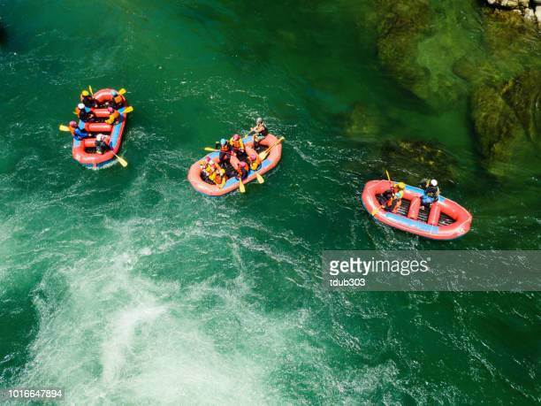 Aerial view of a group of men and women in multiple boats white water river rafting
