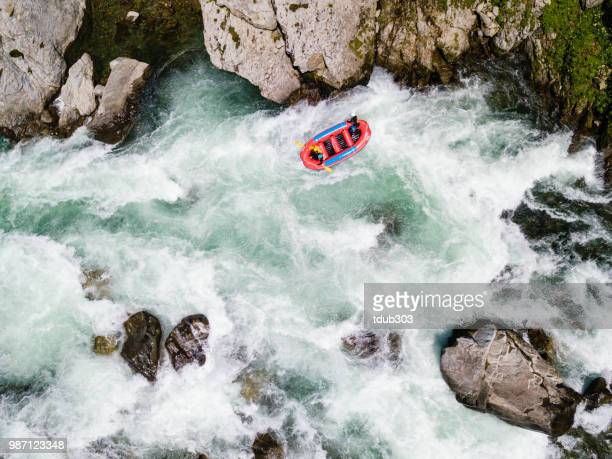 Aerial view of a group of men and women white water river rafting