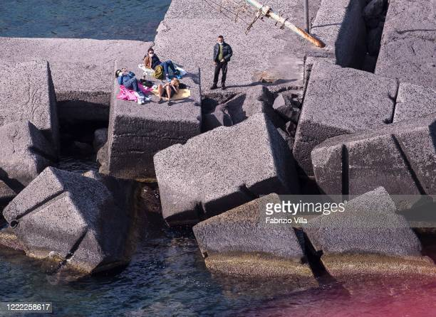 Aerial view of a group of people wearing protective masks at the sea among the rocks sunbathing on May 01 2020 in Catania Italy Italy is still on...