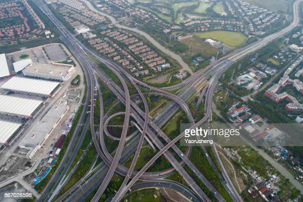 Aerial view of a highway overpass in Shanghai with village, China.