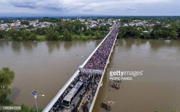 TOPSHOT Aerial view of a Honduran migrant caravan heading to the US as it is stopped at a border barrier on the GuatemalaMexico international bridge...