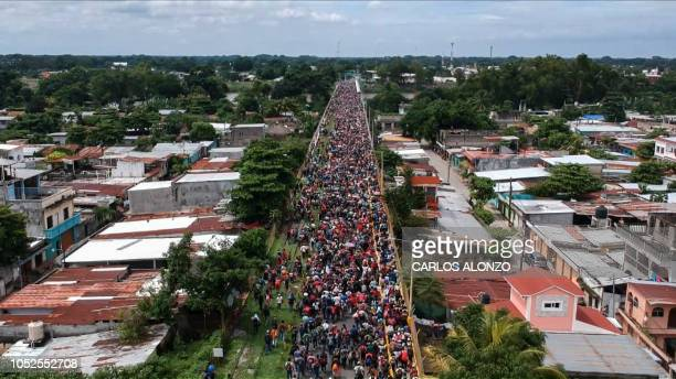 TOPSHOT Aerial view of a Honduran migrant caravan heading to the US as it reaches the GuatemalaMexico international bridge in Tecun Uman Guatemala on...
