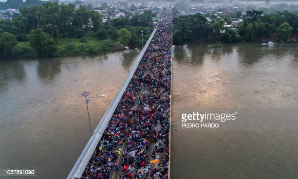 Aerial view of a Honduran migrant caravan heading to the US, on the Guatemala-Mexico international border bridge in Ciudad Hidalgo, Chiapas state,...