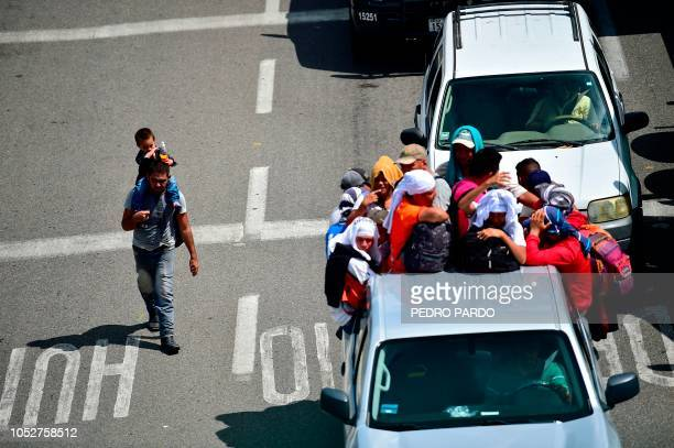 Aerial view of a Honduran migrant man carrying a child as fellow men onboard a truck take part in a caravan heading to the US in the outskirts of...