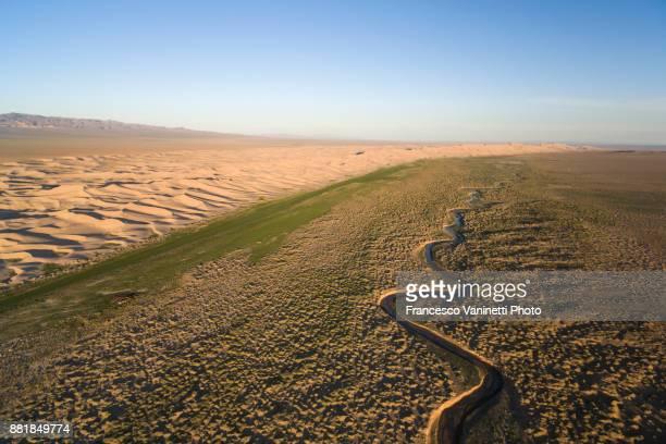 Aerial view of a Khongoriin river and Khongor dunes in Gobi Gurvan Saikhan National Park. Sevrei district, South Gobi province, Mongolia.