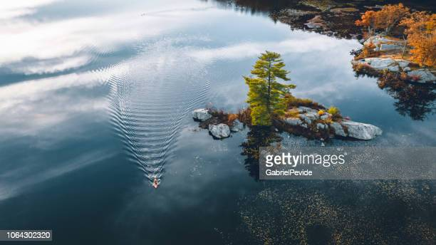 aerial view of a lake with a man in the canoe - kayak stock pictures, royalty-free photos & images