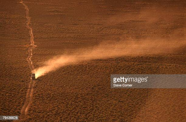 aerial view of a landrover on a dirt road with a dust trail. karoo, western cape province, south africa - the karoo stock photos and pictures
