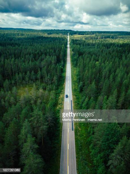 aerial view of a long straight of a country road in the middle of a forest in finland - 道 ストックフォトと画像