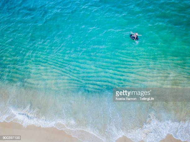 Aerial view of a man floating with a Toucan on the sea