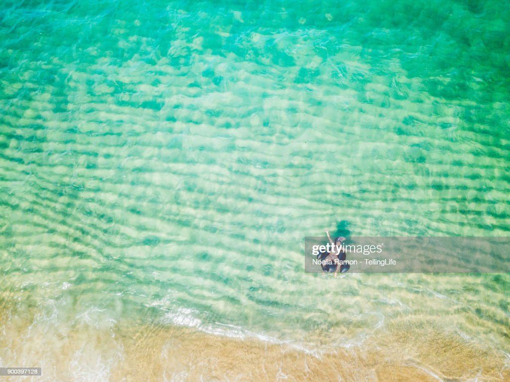 Aerial view of a man floating with a Toucan on the sea : Stock Photo