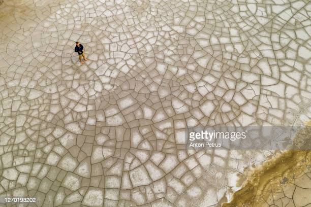 aerial view of a man on the cracked ground. global warming concept - damaged stock pictures, royalty-free photos & images
