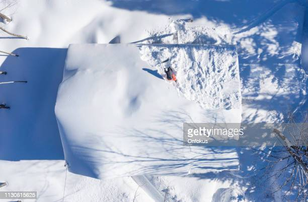 aerial view of a man shoveling snow from a house roof top after snowstorm - house collapsing stock pictures, royalty-free photos & images